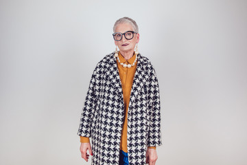 Stylish and elegant old woman in glasses on a white background.