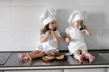 two little baker girls are drinking tea with a pabcakes in the kitchen