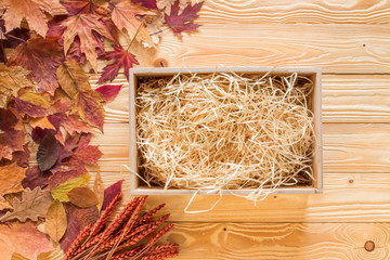 opened box with straw on wooden background decorated by  fallen leaves, top view