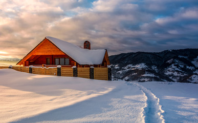 path to wooden chalet in deep snow at sunrise. gorgeous landscape in winter mountains, great place for vacation