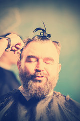 A bearded man with a clip on the head in a hairdressing salon