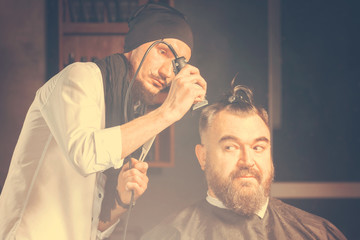 Hairdresser in a black cap and a black apron cuts with hairclipper a man with a clip on the head