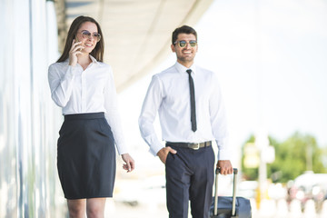 The business man and woman phone and walk with a suitcase
