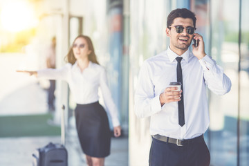 The handsome businessman in sunglasses phone near the woman