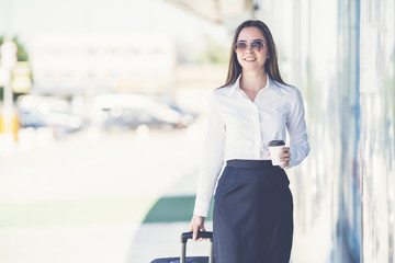 The beautiful businesswoman in sunglasses walk with a suitcase
