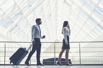 The business man and woman walk with a suitcase