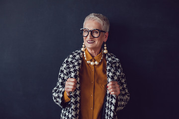 Stylish old woman in glasses standing on a black background.