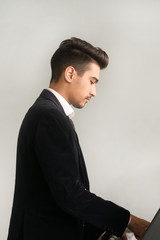 Handsome young man in a black suit, white shirt and tie