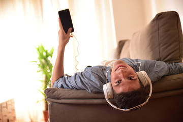 Teen lying face up reclining on couch listening to music