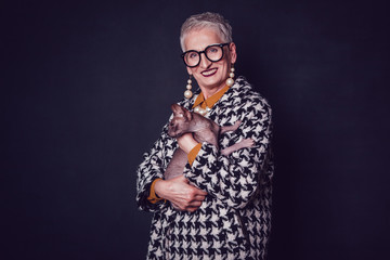 Stylish old woman in glasses holds a Sphynx cat on a black background.