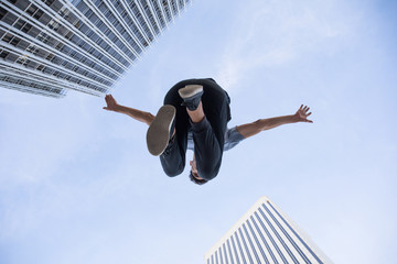 From below shot of man in moment of jumping high on background of skyscrapers and blue sky.