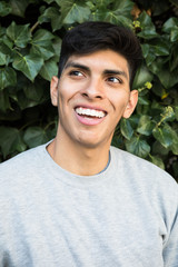 Portrait of young man in gray casual pullover laughing happily and looking away on background of bushes.