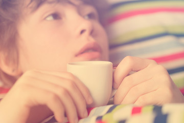 Cute teenager girl lying in bed with a cup of coffee in hand. Toned