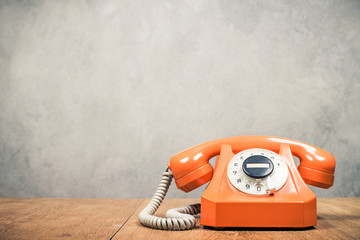 Retro outdated orange rotary telephone on wooden desk front textured concrete wall background. Vintage old style filtered photo