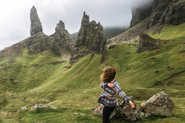 Young woman in wool sweather standing in front of the mountain landscape Old Man of Storr in Scotland