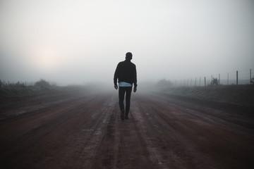 Man walking on misty path Wall mural