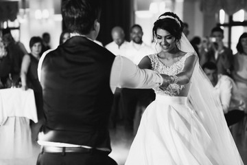 Bride and groom hold each other hands dancing in the hall