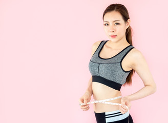 Young asian beautiful woman with sport fitness concept, workout, exercise, measure tape at waist on pink background
