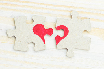 Broken heart made of two pieces of jigsaw puzzle on light wooden table, close-up