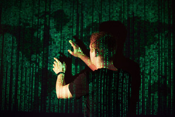 Double exposure of a caucasian man and Virtual reality VR headset is presumably a gamer or a hacker cracking the code into a secure network or server, with lines of code