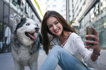 Young woman with dog In city. Teenager girl taking self picture with her dog.