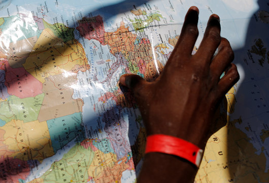 A migrant looks at a map as he rest in the MV Aquarius rescue ship after being rescued by SOS Mediterranee organisation, during a search and rescue (SAR) operation in the Mediterranean Sea, off the Libyan Coast
