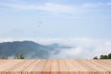 Wood table top on background of mountain view in the morning - can be used for display or montage your products