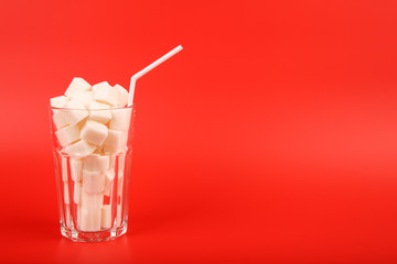Glass full of sugar cubes isolated on red background - unhealthy eating concept
