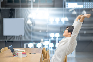 Young Asian man stretching out his arm during working with laptop computer in workspace. High school or university college student, educational concept