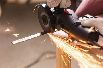 Worker Using Angle Grinder in Factory and throwing sparks.