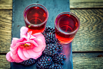 Homemade berry liqueur with fresh ripe blackberries, pink flower and black stone tray on wooden background. Sweet alcohol drink.