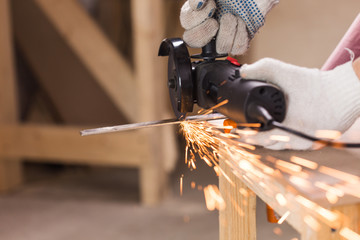 Heavy industry worker cutting steel with angle grinder