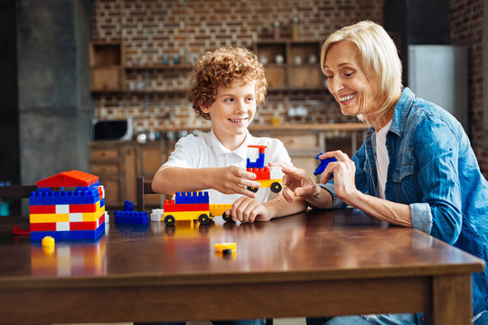 Radiant granny helping her grandson with car building