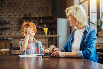 Smiling grandma looking at grandson fooling with pencil