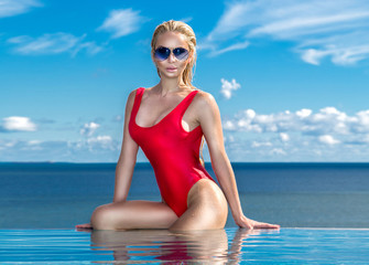 Beautiful blonde woman model with wet hair and elegant makeup sitting in a pool with amazing views in a luxury hotel, wearing jewelry, earrings with the crystals and wet naked body