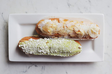 Pistachio and almond eclair, traditional French dessert, on marble background
