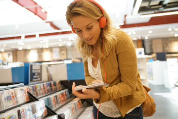 Woman in multimedia store testing new music discs