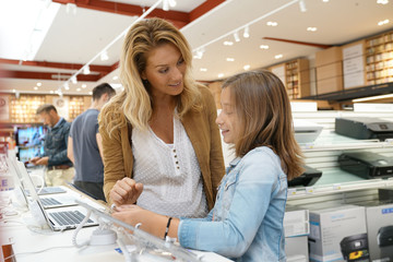 Mother and daughter in multimedia store looking at tablets