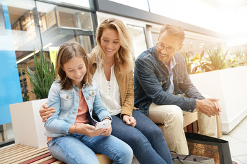 Family on shopping day in mall, sitting on public bench