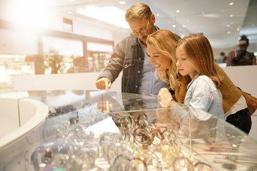 Family in shopping mall looking at jewelry department