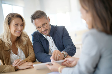 Mature couple meeting real-estate agent in office