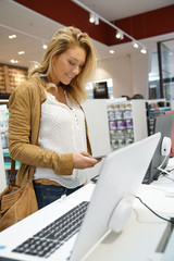 Woman in multimedia store looking at smartphones