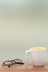 cup and eyeglass on the table