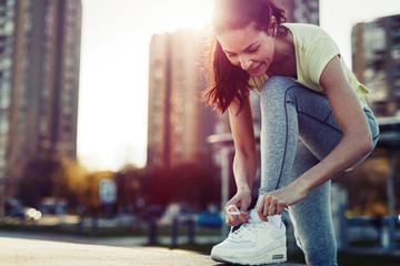Attractive sportswoman tying shoelace and getting ready for fitness