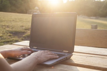 Unrecognizable woman working outdoor on her laptop. Sunset positive vibe. Relaxed business. Notebook mockup , display replaceable with your design.