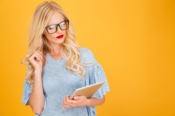 Serious young blonde woman using tablet computer.