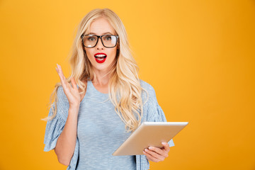 Confused young blonde woman using tablet computer