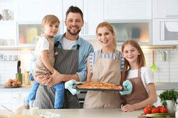 Family with pizza in kitchen. Cooking classes concept