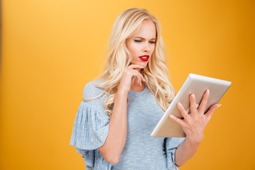 Confused young blonde woman using tablet computer.