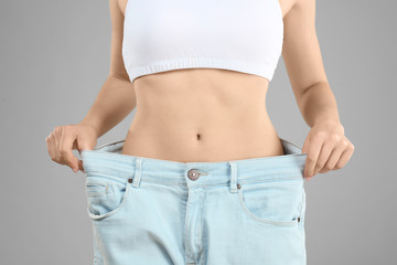 Young woman in oversized jeans on gray background, closeup. Diet concept